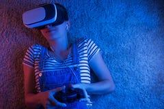 Een meisje met een gamepad die in vrglazen, met blauw en rood licht spelen Het concept innovatie en de toekomst royalty-vrije stock afbeeldingen