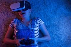 Een meisje met een gamepad die in vrglazen, met blauw en rood licht spelen Het concept innovatie en de toekomst royalty-vrije stock foto