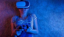 Een meisje met een gamepad die in vrglazen, met blauw en rood licht spelen Het concept innovatie en de toekomst stock afbeeldingen