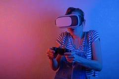 Een meisje met een gamepad die in vrglazen, met blauw en rood licht spelen Het concept innovatie en de toekomst stock fotografie