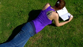 Een meisje met glazen leest een boek stock videobeelden