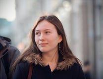 Een meisje met een glimlach die een voorbijganger bekijken stock afbeeldingen