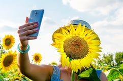 Een meisje met haar haar beneden en hoedenplanken onder het gebied met zonnebloemen stock foto's