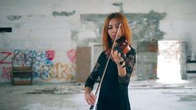 Een meisje met houten viool presteert in een lege ruimte stock footage