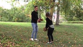 Een meisje met een kerelgang in het park en werpt op de herfstbladeren stock footage
