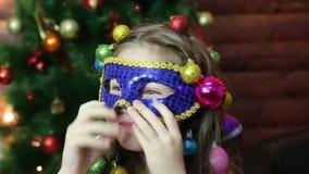 Een meisje met Kerstmisslingers op haar hoofd in een Carnaval-masker stock videobeelden