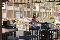 Een meisje met een koffer roept een taxi aan de luchthaven Royalty-vrije Stock Foto's