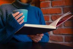 Een meisje met koffie en een boek stock afbeeldingen