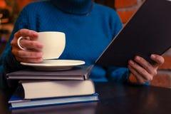 Een meisje met koffie en boeken stock foto