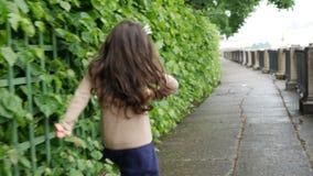 Een meisje met een kroon op haar hoofd loopt in de de zomertuin stock videobeelden