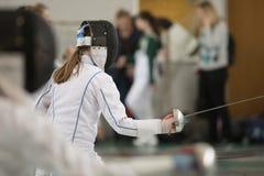 Een meisje met lang haar die het schermen duel op toernooien hebben Een meisje die een sabel houden stock foto's