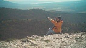 Een meisje met lang haar in een geel jasje en een grijs GLB bevindt zich in de bergen en kijkt door een telescoop stock video