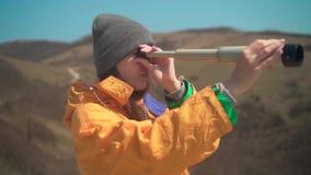 Een meisje met lang haar in een geel jasje en een grijs GLB bevindt zich in de bergen en kijkt door een telescoop stock videobeelden