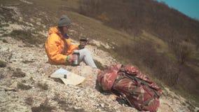 Een meisje met lang haar in een geel jasje, een grijs GLB, glazen zit op een berg, giet thee van een thermosfles stock footage