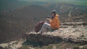 Een meisje met lang haar in een geel jasje, een grijs GLB, glazen zit op een berg, giet thee van een thermosfles, toen dranken stock video