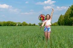 Een meisje met lang haar houdt in haar handen een gekleurd windmolenstuk speelgoed op een groen gebied op een zonnige dag stock afbeeldingen
