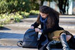 Een meisje met lang haar zit buiten op de stappen stock foto