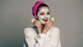 Een meisje met een masker op haar gezicht en een handdoek op haar hoofd behandelt haar ogen met komkommers op een grijze achtergr stock videobeelden