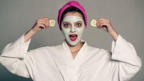 Een meisje met een masker op het gezicht en een handdoek op haar hoofd sluit haar ogen met komkommers op een grijze achtergrond V stock video