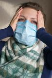 Een meisje met een medisch masker op haar gezicht houdt haar hoofd stock afbeelding