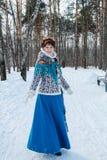 Een meisje met mooi haar op haar hoofd in een Slavische stijl in de volledige groei in het de winterbos royalty-vrije stock foto