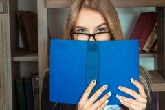 Een meisje met mooie ogen en een boek in zijn handen stock foto's