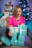 Een meisje met Nieuwjaargiften en Kerstmisboom op de achtergrond royalty-vrije stock afbeeldingen