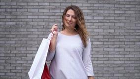 Een meisje met pakketten na het winkelen met een goede stemming tegen een muur van stenen Langzame Motie HD stock videobeelden