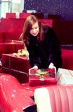 Een meisje met rood haar houdt een doos met een gift, die op een rode auto ligt Het concept feestelijke stemming en aardige gifte royalty-vrije stock foto's