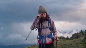 Een meisje met een rugzak en een trekking plakt reizen in de bergen De vallei, met lage wolken die de sneeuw behandelen stock videobeelden