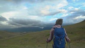 Een meisje met een rugzak en trekkingsstokken bevindt zich en bewondert de mooie bergmening die heeft geopend De vallei stock videobeelden