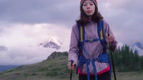 Een meisje met een rugzak, een koplamp en een trekking plakt reizen in de bergen in de avond De vallei, met laag stock videobeelden