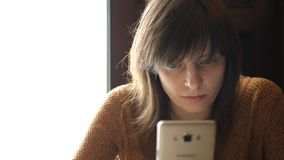 Een meisje met een smartphone in haar handen stock footage