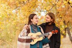 Een meisje met een ukelele in haar handen bekijkt de kerel naast een de herfstachtergrond stock fotografie