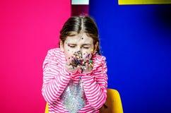 Een meisje met vlechten blaast uit confettien Stock Afbeeldingen