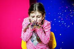 Een meisje met vlechten blaast uit confettien Stock Foto