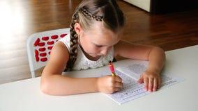 Een meisje met vlechten op haar hoofd voert aandachtig haar thuiswerk bij de lijst uit stock videobeelden