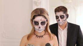 Een meisje met een vreselijke samenstelling in de vorm van een schedel, op de achtergrond is mens stock footage