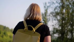 Een meisje met een zak achter haar gaat langs de dijk van de rivier en kijkt in haar richting Achtermening in motie stock video