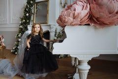 Een meisje in een mooie kleding op een stoel dichtbij de piano stock foto