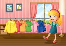 Een meisje naast de hangende kleren binnen het huis Stock Fotografie