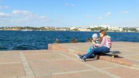 Een meisje neemt beelden van een kind op een smartphone dichtbij het overzees stock video
