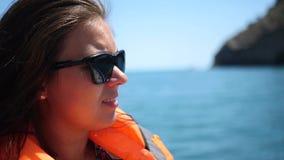 Een meisje op een boot in een vest slingert op zee door golven HD, 1920x1080 Langzame Motie stock footage