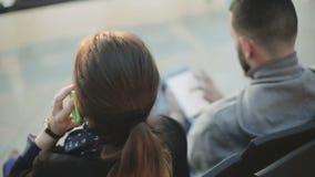 Een meisje op de telefoon spreken en een jonge mens die een tablet gebruiken stock video