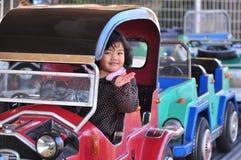 Een meisje op een auto in een pretpark Stock Foto's