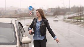 Een meisje op een lege regenachtige weg vraagt om hulp en houdt op voorbijgaand auto's stock videobeelden