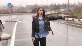 Een meisje op een lege regenachtige weg vraagt om hulp en houdt op voorbijgaand auto's stock footage