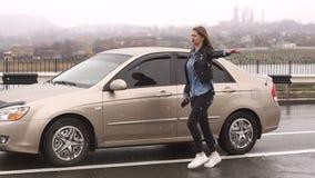 Een meisje op een lege regenachtige weg vraagt om hulp en houdt op voorbijgaand auto's stock video