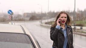 Een meisje op een lege regenachtige weg vraagt om hulp met telefoon en houdt op voorbijgaand auto's stock videobeelden