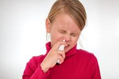 Een meisje overwint zijn vrees en gebruikt neusdienevel op wit wordt geïsoleerd stock afbeeldingen